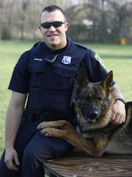 Patrolman 1st Class Anthony Dawson poses this morning with Benny, his K-9 partner. The South Bend Police Department named Dawson its 2012 officer of the year this month, citing his work as a detective with the departments burglary unit and transition to his new job as a K-9 handler. (South Bend Tribune/SANTIAGO FLORES)