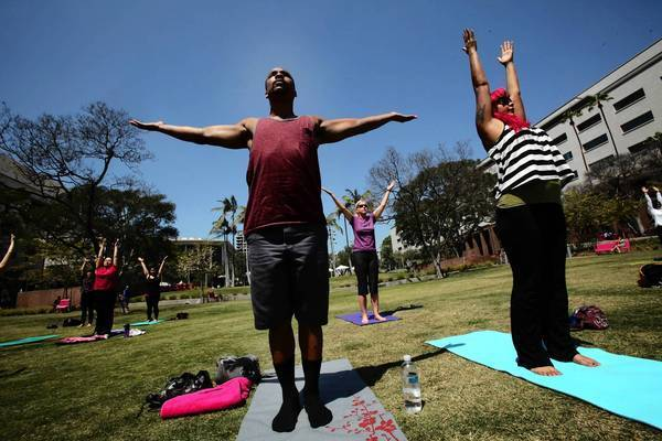Jovon Washington, left, and Nay Jospine, both of Echo Park, participate in a free yoga class on the lawn at Grand Park.