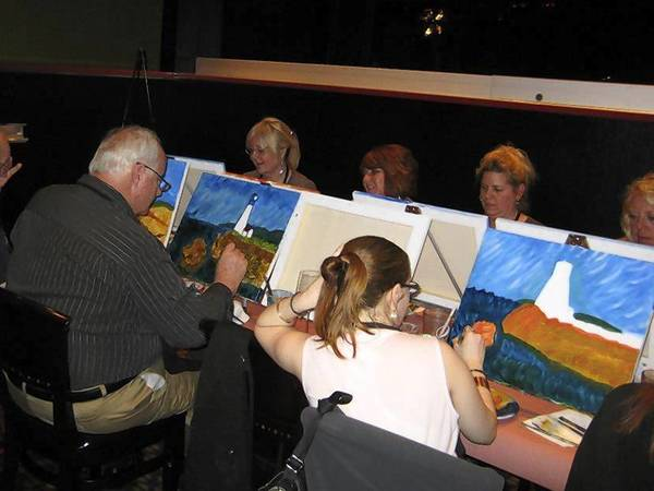 Participants try their hand at painting during a Vino van Gogh event at Aurelio's pizza in Naperville.