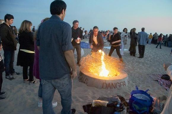 Beachgoers enjoy a fire in Corona del Mar. Supporters of the threatened tradition of beach fire rings gathered Sunday in nearby Huntington Beach.