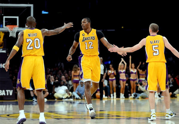 Lakers' Dwight Howard (12) celebrates his basket with guards Jodie Meeks and Steve Blake.
