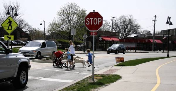Pedestrians cross Harlem Avenue near the Glenview Public Library on April 29.