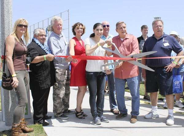 In The Pipeline essay contest winner Samar Saad, a junior at Fountain Valley High School, cuts the opening ribbon at the 2013 Taste of Huntington Beach. With her is City Councilman Joe Carchio and third from the left is music legend Dean Torrence.