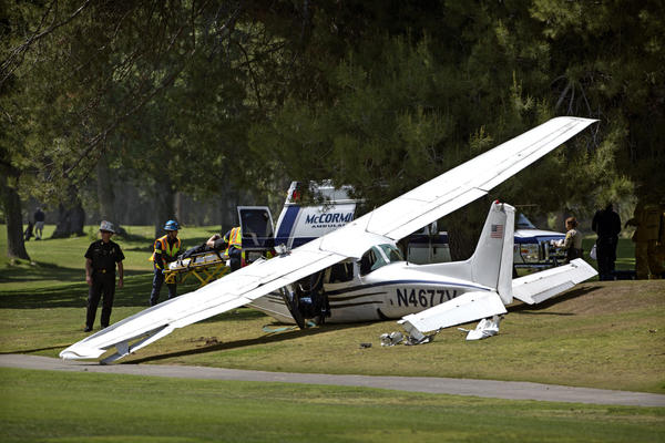 A victim is loaded into an ambulance at the scene of a single-engine plane crash at Westlake Golf Course.