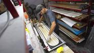 On an early Wednesday morning, Signal Snowboards employee Stephen Rezendes applies a coat of epoxy resin to the board he's building, getting a head start for the company's 2013-14 season.