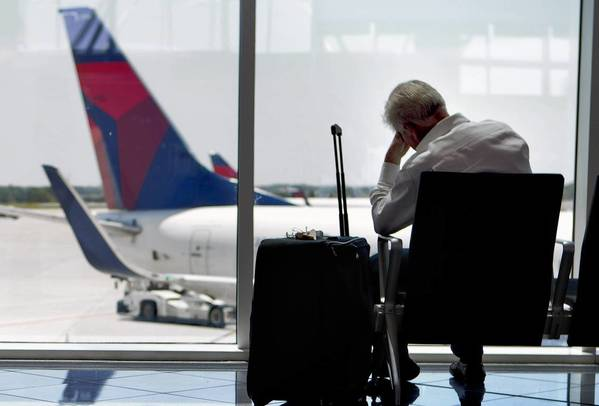 A traveler, right, waits at Hartsfield-Jackson Atlanta International Airport.