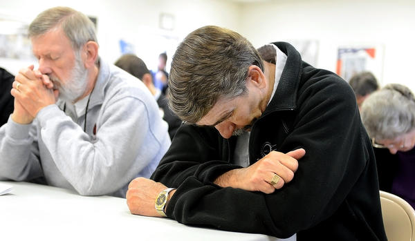 Larry Barron, left, and Dave Dopp take part in a prayer during a Workers Memorial Day ceremony held at the Central Maryland AFL-CIO Labor office on Monday.