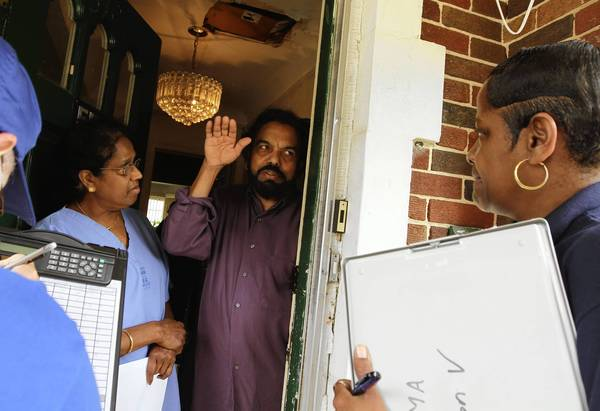 Susamma and Mathai Thomas describe their basement water damage Monday to Carolyn Robinson-Tucker, right, of the Federal Emergency Management Agency. Federal, state and local officials were visiting Chicago's Albany Park neighborhood to assess the severity of area flooding.