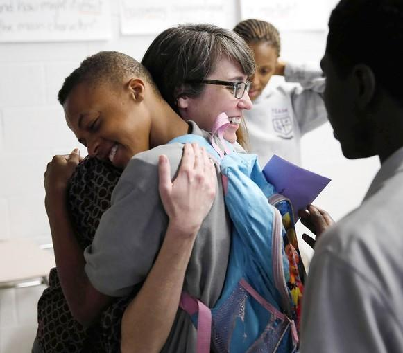 Katherine Dube, an English teacher at TEAM Englewood Community Academy, hugs freshman Armani Brown, 15, on Monday after she received a Golden Apple Award.