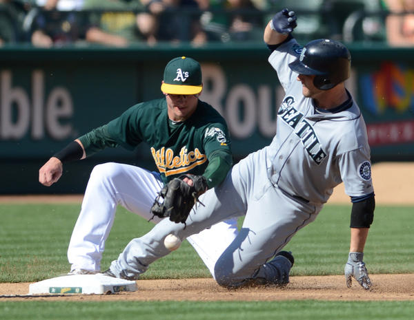 The Athletics' Josh Donaldson can't get control of the ball and Seattle Mariners' Casper Wells is safe at third with a triple.