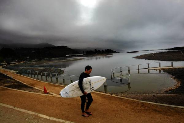 A surfer makes his way down a groomed path around the newly restored Malibu Lagoon. The $7-million project has been long in the making — two decades and counting. Depending on whom you talk to, the lagoon has been restored — or ruined.