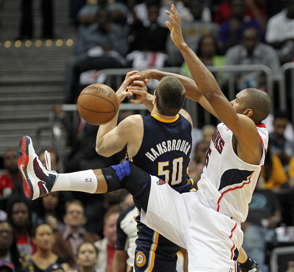 The Hawks' Al Horford knocks the ball away from the Pacers' Tyler Hansbrough during first-half action.