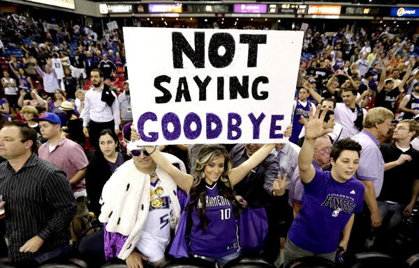 A Sacramento Kings fan holds up a sign expressing her hopes that the team won't move.