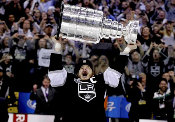 Los Angeles Kings' Dustin Brown hoists the Stanley Cup last June.