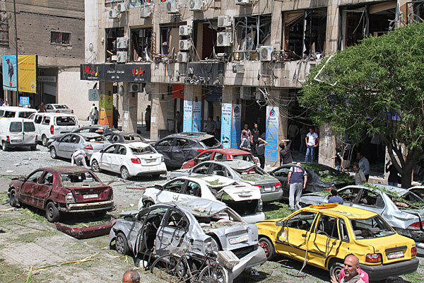 Damaged cars are seen at the scene of an explosion in the heart of Damascus.