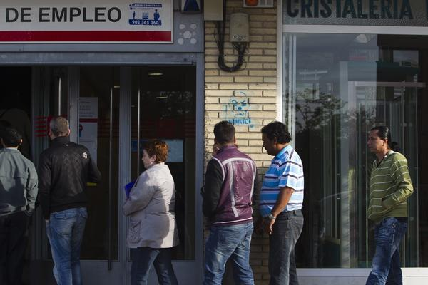 Job seekers enter an employment office in Madrid as it opens for the day.
