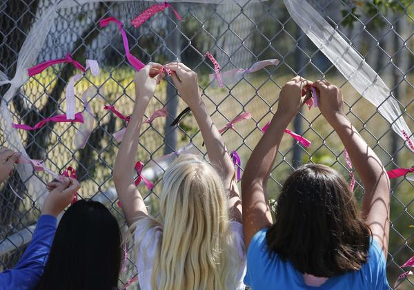 Students at Valley Spring's Jenny Lind Elementary School tie ribbons Monday honoring their classmate, 8-year-old Leila Fowler, who was fatally stabbed in her family's home.