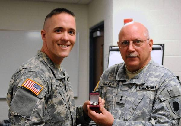 Illinois Army National Guard Sgt. 1st Class Daniel Neville of Plainfield, left, was presented the Director's 54 Ring by Maj. Gen. Dennis Celletti of Springfield, the Assistant Adjutant General of the Illinois Army National Guard April 11 at Camp Lincoln in Springfield.