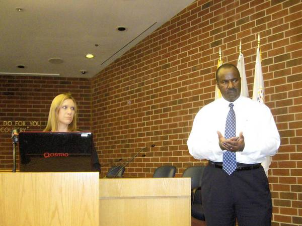 Niles Acting Assistant Village Manager Cathy Doczekalski looks on as energy consultant Emmit George speaks at a public hearing on electric aggregation Monday evening.