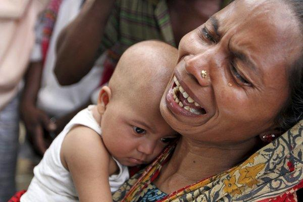 A woman holds her daughter as others hold photographs of relatives who they believe are trapped after a building collapsed on the outskirts of Dhaka, Bangladesh.