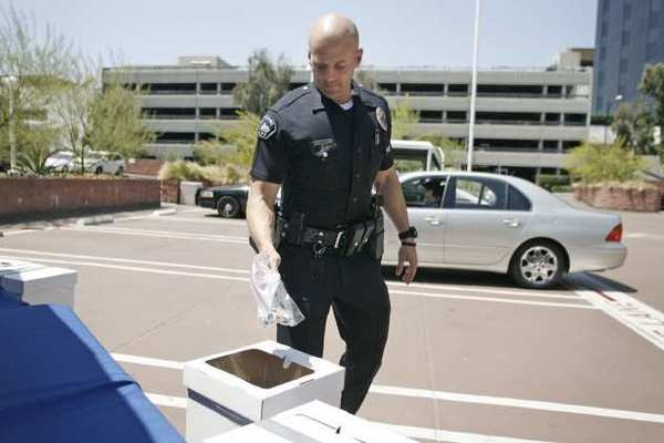 Burbank Police Officer Joshua Kendrick takes prescription drugs from residents during the event on Saturday.