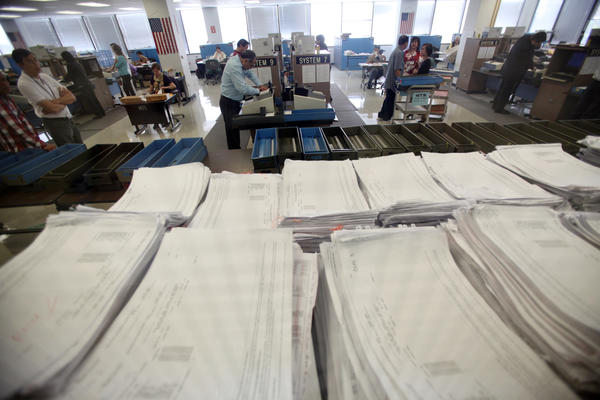 County workers load ballots into computers at the registrar recorder's office in Norwalk after the November 2012 election. Election officials said that adding school district elections to the already-crowded November ballot would exceed their ability to conduct elections.