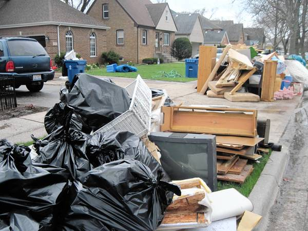 Furniture ruined by flooding is piled on the curb in Elmhurst.