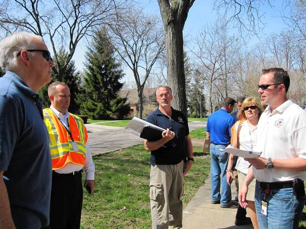 Jared Owen (far right) of Illinois Emergency Management Agency and other local officials speak to a Downers Grove resident about damage to homes on Grand Avenue.