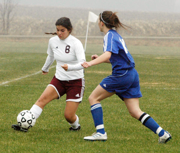 Charlevoix sophomore Olivia Storm (8) looks to get around a Kalkaska defender during Monday's Lake Michigan Conference match at the Charlevoix High School soccer field. The Rayders defeated the Blazers, 8-0.
