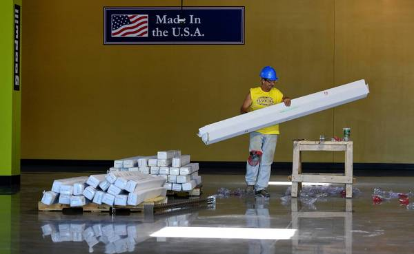 Shawn Towle works to install a wall and floor system that will eventually hold clothing and other products inside of the Goodwill under construction on Lake Underhill Rd. in Orlando on April 30, 2013. The store is made almost entirely of American-made products.