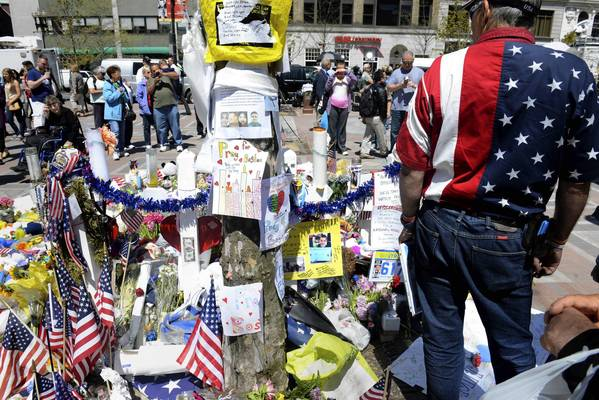 Visitors stop by the makeshift memorial in Copley Square dedicated to the victims of the Boston Marathon bombings.