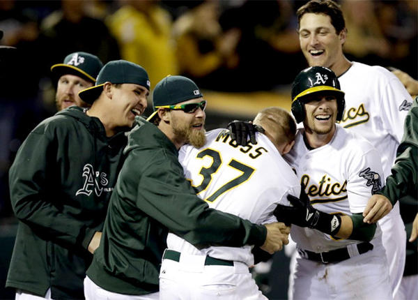 Oakland Athletics players celebrate after Brandon Moss hit a game-winning, two-run home run in the bottom of the 19th.