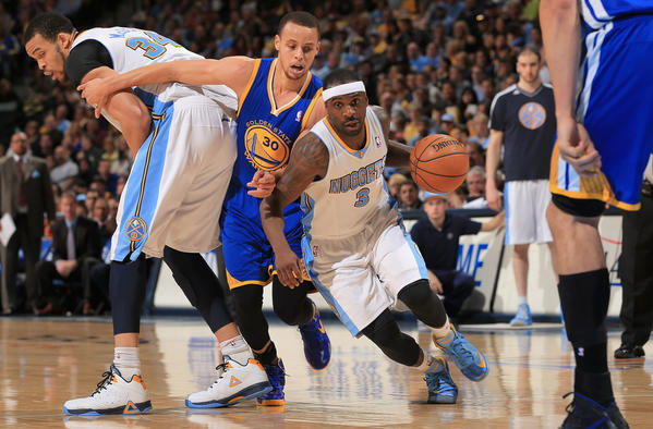 The Nuggets' Ty Lawson drives past the Warriors' Stephen Curry with the help of a screen from JaVale McGee.