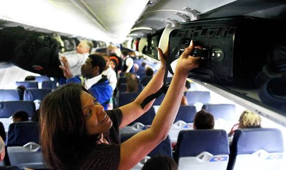 Passenger stows her luggage in overhead compartment