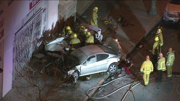 Firefighters work at the scene of a fatal car collision in South L.A.