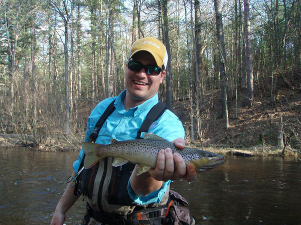 Ethan Winchester, head guide for Boyne Outfitters, holds an early spring brown trout.