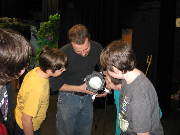 Professional lighting designer, CJ Winnell, explains a lighting instrument to students.