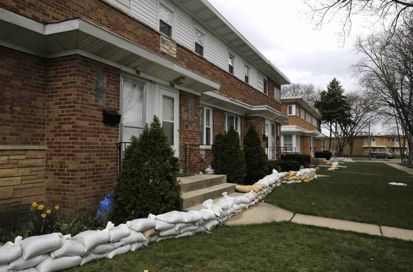 Many homes in Des Plaines, such as these iin the 300 block of Oak Street, suffered serious flooding. Schools, however, appeared to have mostly escaped severe damage.
