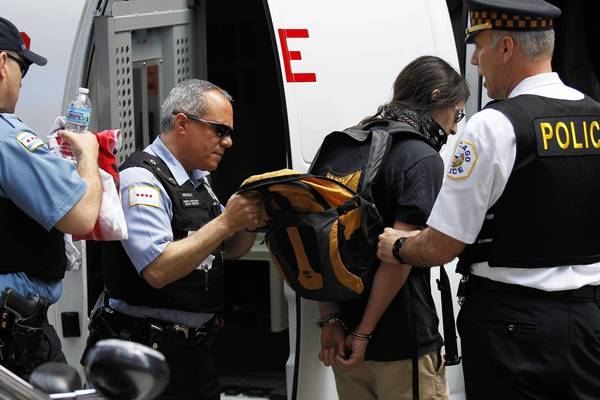 A protester is arrested on Michigan Avenue in Chicago as a group of May Day protesters walk south bound on Michigan Avenue on Wednesday, May 1, 2013.