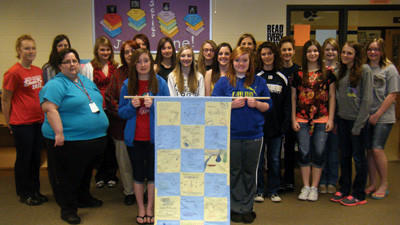 Eighth grade students Samantha Mains (left) and Alexis Custer (right) hold the quilt created by Heidi Klahre's Information Literacy class at Shade-Central City High School. They are flanked by their fellow classmates who also worked on the project, from left, first row: librarian Heidi Klahre, educational consultant Pam Weyant, Sarah Letosky, Natasha Meck, Autumn Fogle, Cayley Gumbita, Jaiden Kimmel. Second row: Shannon Swallow, Elizabeth Rubright, Lauren Jarvis, Rachel Hause, Karley Maurer, Machala Gibbons, Alexis Medva, Myah Koleszarik, Jensen Kimmel and Amber Gibbons. Absent from photo are: Ryleigh Andrews, Courtney Dona, Bella Faidley, Katlyn Havyer and Rikki Hutchinson.