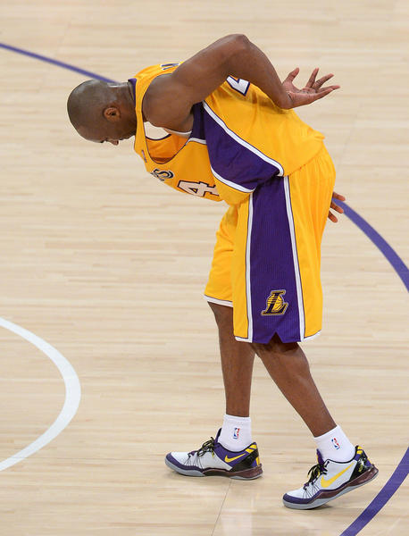 Los Angeles Lakers shooting guard Kobe Bryant (24) tries to walk off an injury to his right ankle in the first half of the game at the Staples Center.