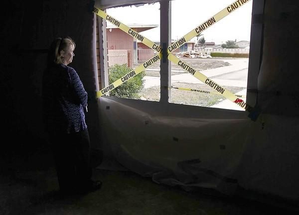 Laura Walsh Jones, an alumni who attended school at Wardlow School in Huntington Beach from 1972 to 1974, looks out a window during a tour of the rundown campus one last time before developers demolish it in May.