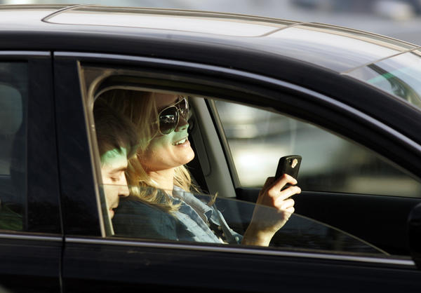 A motorist appears to be texting while driving through Santa Monica and Wilshire boulevards in Beverly Hills.