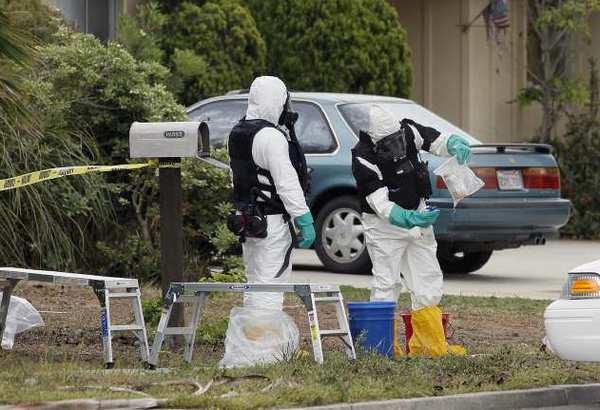 Bomb squad personnel bag up materials from inside a home at 3152 Bermuda Drive in Costa Mesa on April 15.