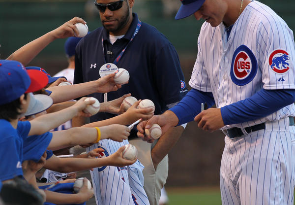Chicago Cubs fans vie for Anthony Rizzo's autograph before the Cubs play the San Diego Padres at Wrigley Field in Chicago.