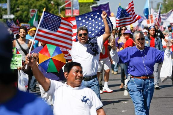 People make their way along Paseo de la Plaza in downtown Los Angeles at the conclusion of a May Day march for immigration reform.