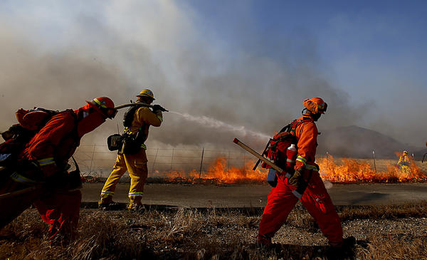 Firefighters battle the Banning brush fire Wednesday afternoon.