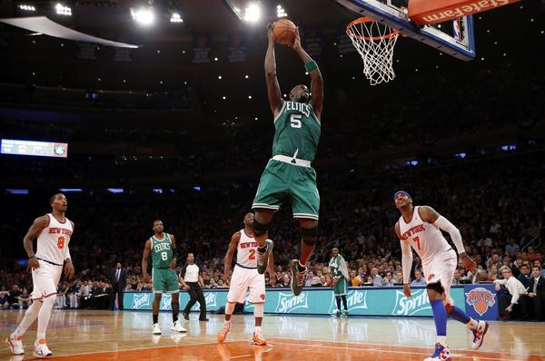 The Celtics' Kevin Garnett drives for a dunk past the Knicks' Carmelo Anthony and J.R. Smith during the first quarter.