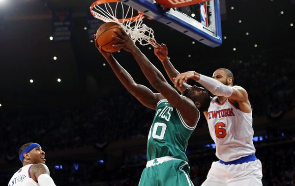 Boston Celtic Brandon Bass is fouled by New York Knick Tyson Chandler as Bass drives to the basket during the first quarter in Game 5 of their NBA Eastern Conference basketball playoff series in New York.