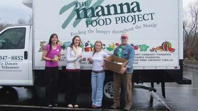 Jenna Williams (from left) and Sarah Hagen of Castle Farms present Katlyn Cosens and Patrick Nagi of The Manna Food Project with a check for $104 and donated food items. The contributions were obtained for Manna during the March and April installments of a monthly workshop series at Castle Farms.